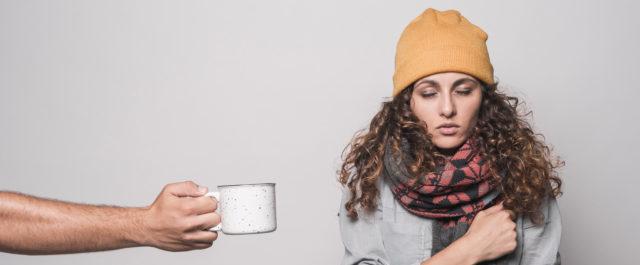 Mano ofreciendo una taza de café a una mujer con apariencia friolera