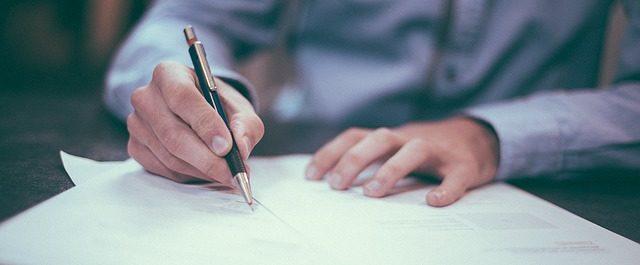 hombre firmando unos papeles